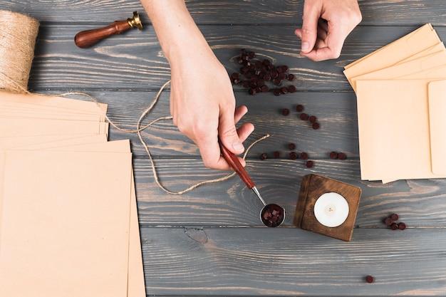 木製の机の上の工芸材料とワックスのスプールを持つ女性の手