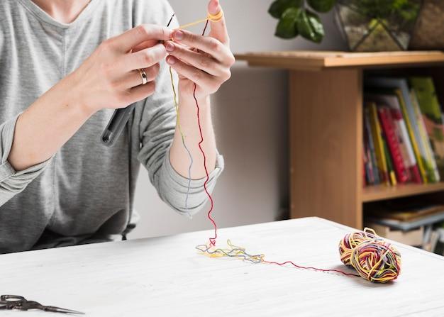 カラフルな糸で編み物をする女性の手