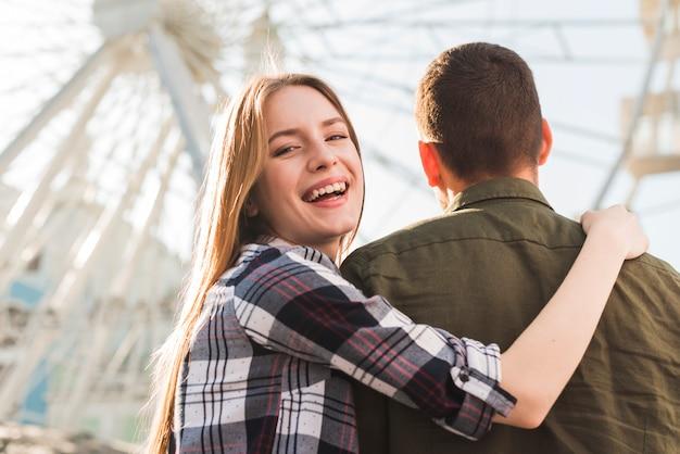 観覧車の前で彼女のボーイフレンドと一緒に立っている笑顔の女性の背面図