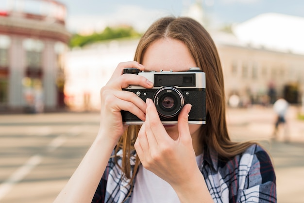 カメラで写真を撮る若い女性の肖像画