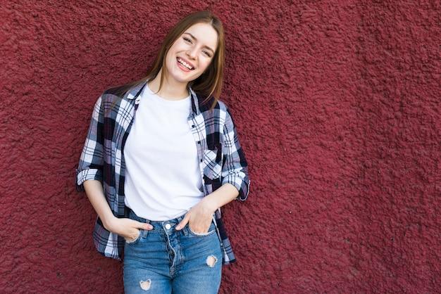 赤の織り目加工の壁にもたれてファッショナブルな幸せな女