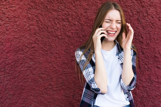 Красивая молодая женщина разговаривает по смартфон с счастливым выражением лица