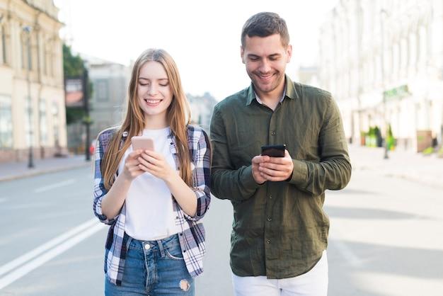Улыбающиеся друзья мужского и женского пола, с помощью мобильного телефона белый ходить вместе на улице