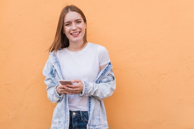 Стильная счастливая женщина держит мобильный телефон, глядя на камеру, стоя возле бежевой стены