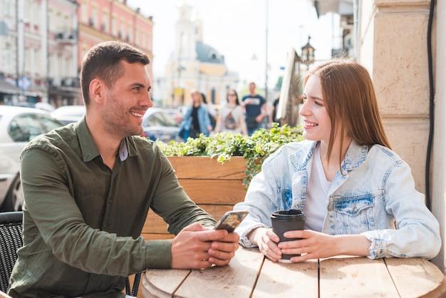 カフェでロマンチックなデートを持っている幸せな若いカップル
