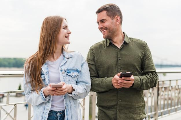 Молодая пара улыбаясь, держа мобильный телефон, глядя друг на друга