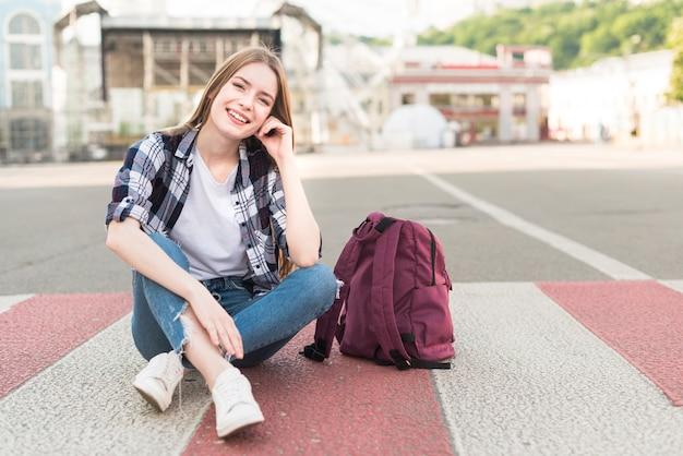 彼女のバックパックが付いている道に座っているファッショナブルな笑顔の女性