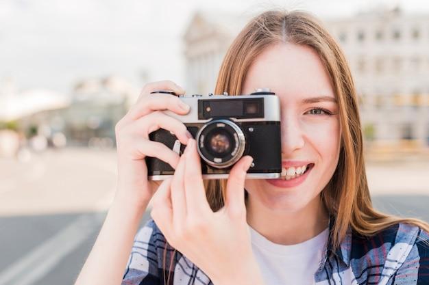 屋外でカメラで写真を撮る若い女性の笑みを浮かべてください。