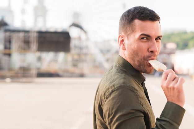 Щетина молодой человек ест мороженое эскимо в парке развлечений