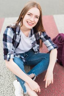 路上に座ってカメラを見て笑顔の女性の高角度のビュー