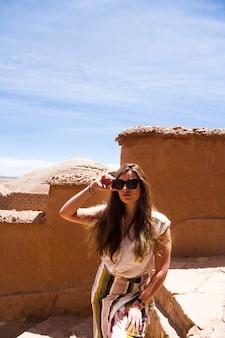 女性が青い空の下で砂漠の遺跡でポーズ