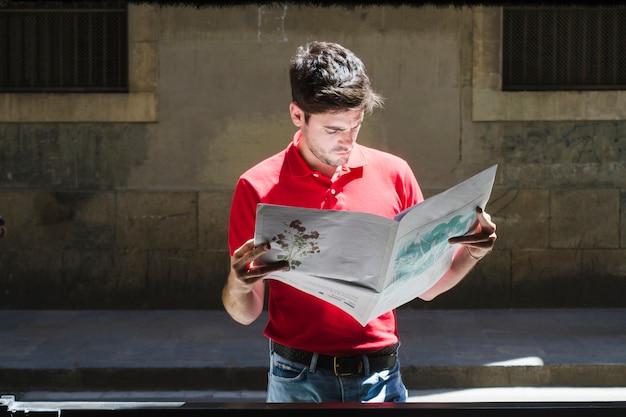 通りで新聞を読んでいる若い男のミディアムショット