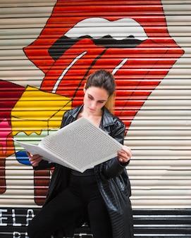 Среднего выстрела стоя женщина читает бумагу