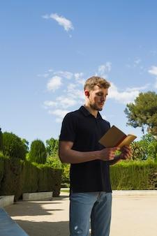 Белокурый мальчик читает в парке