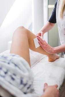 美容院で彼女の足にワックスをかけている女の子