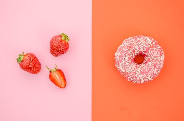 Вид сверху пончик против фруктов