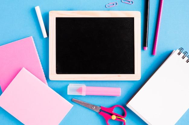 Меловая доска и школьные принадлежности на цветной поверхности