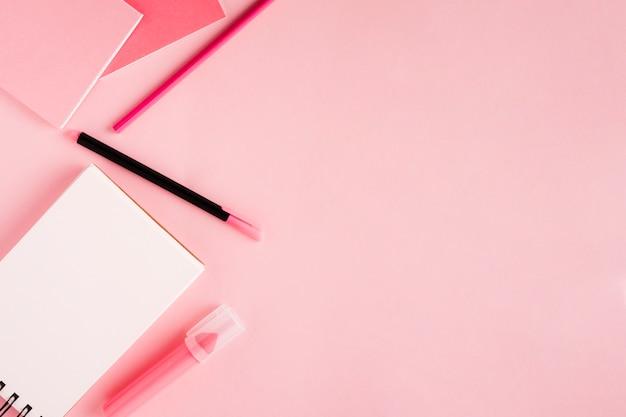 スクラッチパッドと色付きの背景上の文房具
