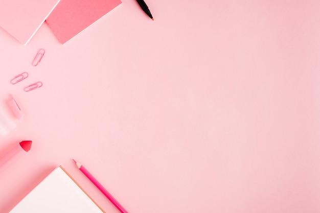 机の上のピンクの学校文房具