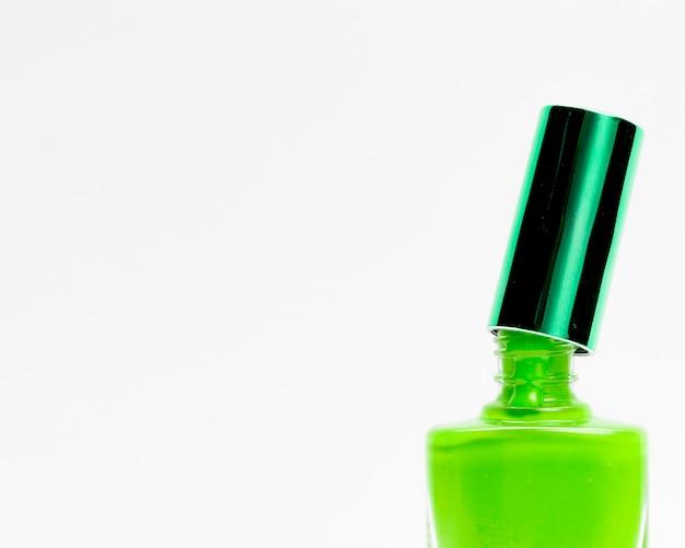 Зеленый лак для ногтей на белом фоне