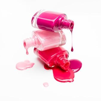 Крупный план бутылок с пролитым лаком для ногтей