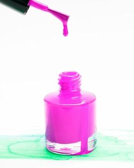 Розовый лак для ногтей капает с кисти в бутылке на фоне