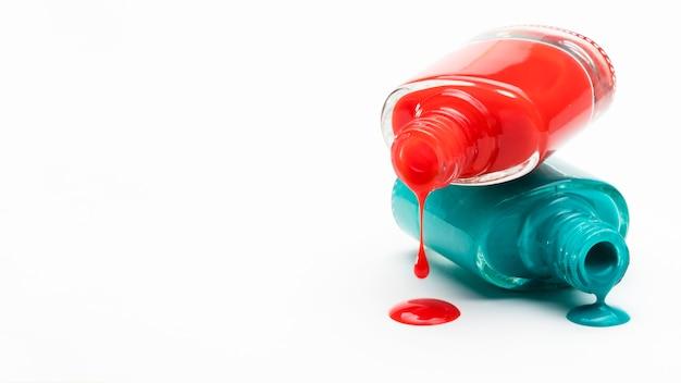 白いコピースペースを背景にボトルからこぼれた赤と緑のマニキュア