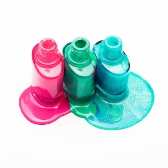 Открытые бутылки с разлитым лаком для ногтей на белой поверхности