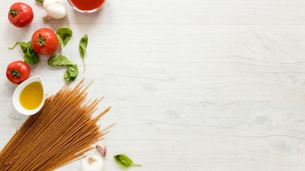 スパゲッティパスタと白いテーブルの上の新鮮な食材