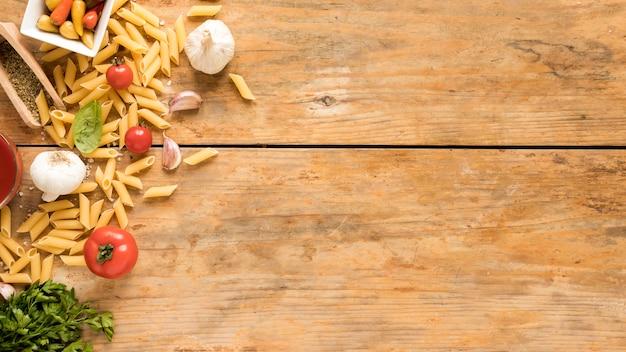 古い木製のテーブルの上の野菜食材とペンネパスタ
