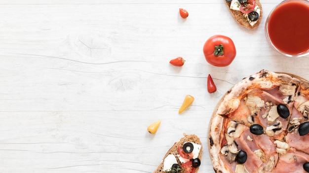 テキストのためのスペースと白い机の上のトマトソースとパンのサンドイッチの近くのおいしいベーコンとキノコのピザ