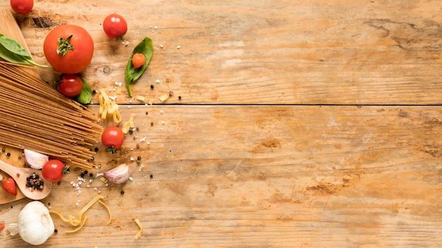 織り目加工のテーブルの上のスパゲッティパスタと新鮮な生のイタリア食材