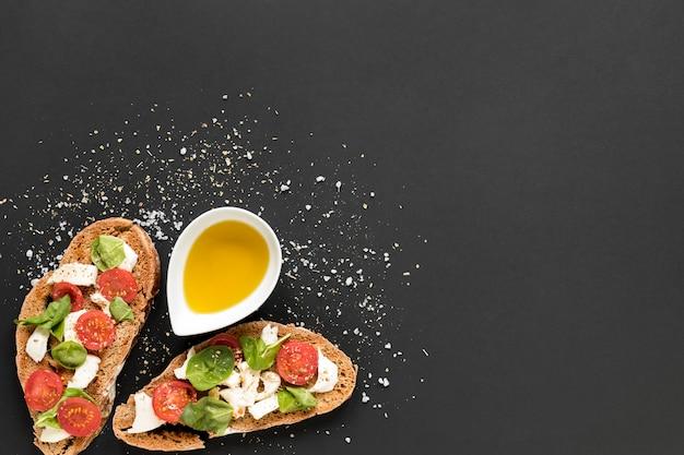 トッピングと黒の背景上のオリーブオイルのおいしいパン