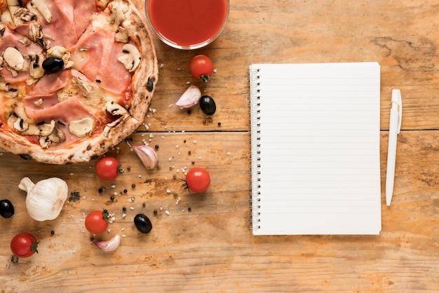 空白のメモ帳と木製のテーブルの上のトマトソースベーコンパスタの近くにペン