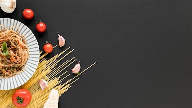 Вкусная итальянская лапша с сырыми спагетти; помидор; зубчики чеснока на черном фоне
