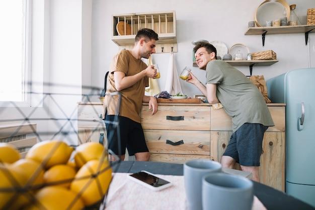 台所でジュースを飲むを楽しんで幸せな友達