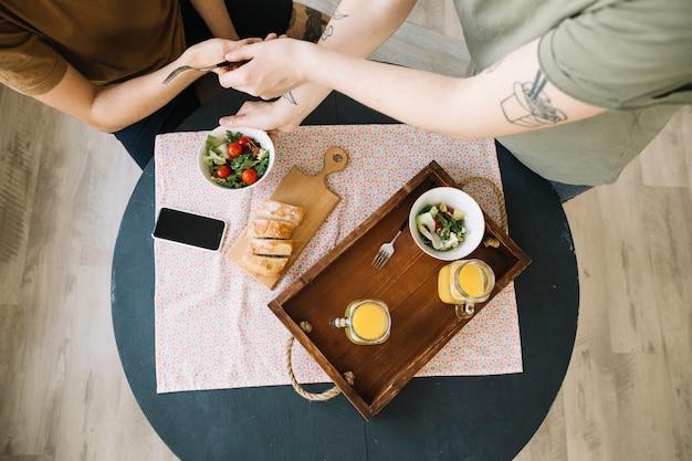 朝食と男性の前のテーブルの上の携帯電話の立面図