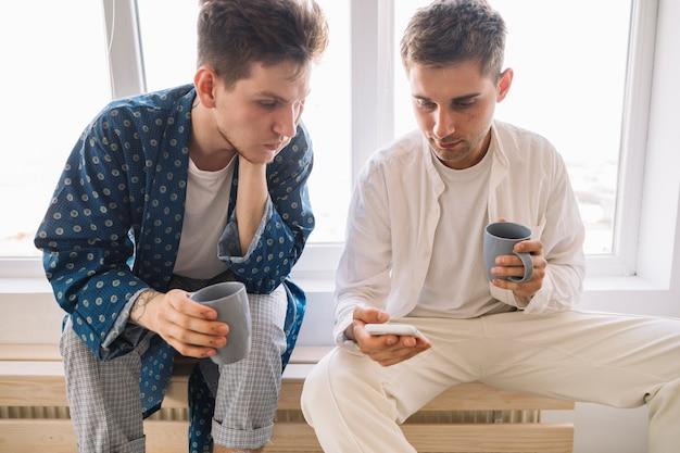 一杯のコーヒーを手に保持している携帯電話で探しているハンサムな男性