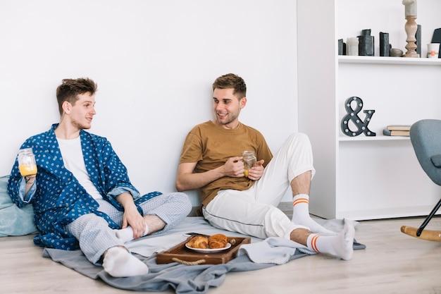 Красивые счастливые мужчины, имеющие завтрак, сидя на полу