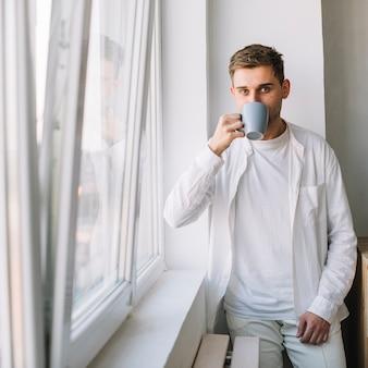 窓の近くに立っている飲み物を飲むハンサムな男のクローズアップ
