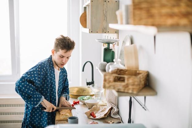 台所でナイフで木製のまな板にパンを切る男