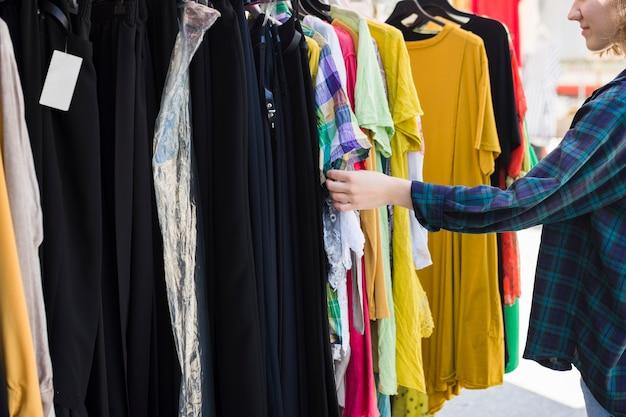 Молодая женщина, выбирая разные наряды