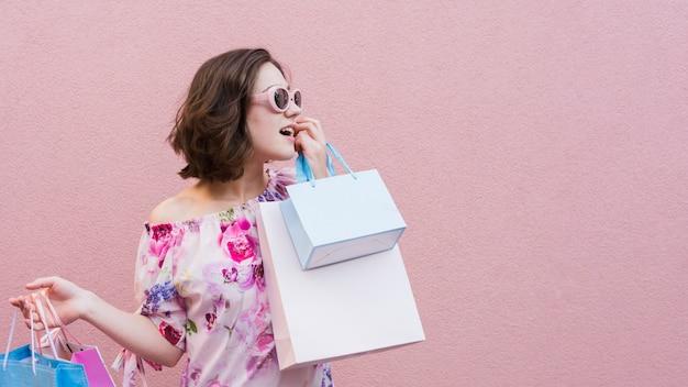 買い物袋を保持している若い女性