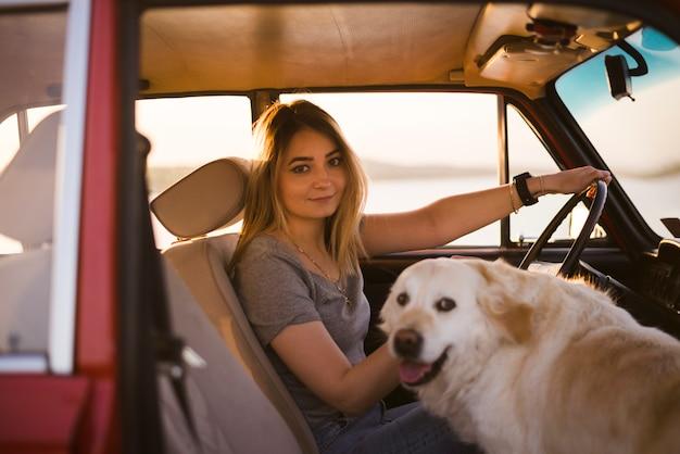 車の中で彼女の犬を持つ女性