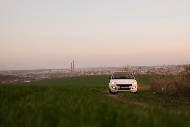 緑の丘の上の車の運転