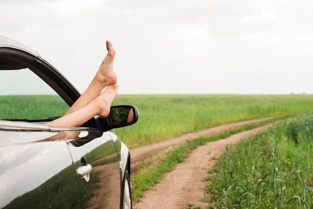 車の窓から外を見ている女性の足