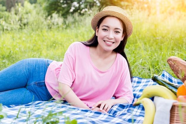 アジアの女性のピクニック布の上に横たわる