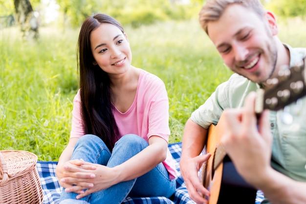 Человек азиатской женщины наблюдая играя гитару