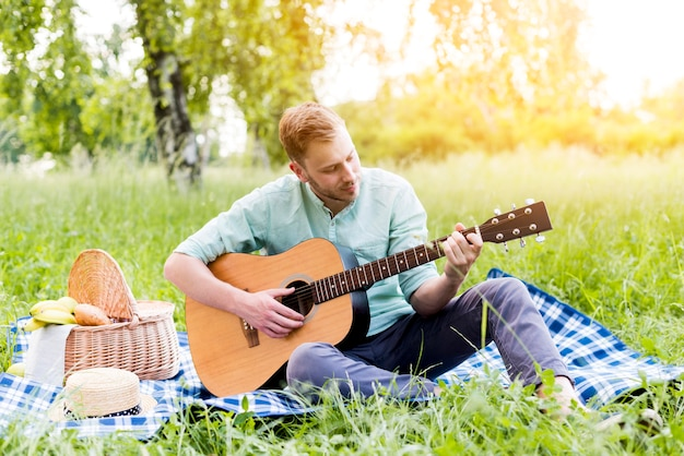 Мужчина играет на гитаре на пикнике летом