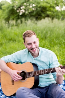 Улыбающийся мужчина играет на гитаре на пикнике